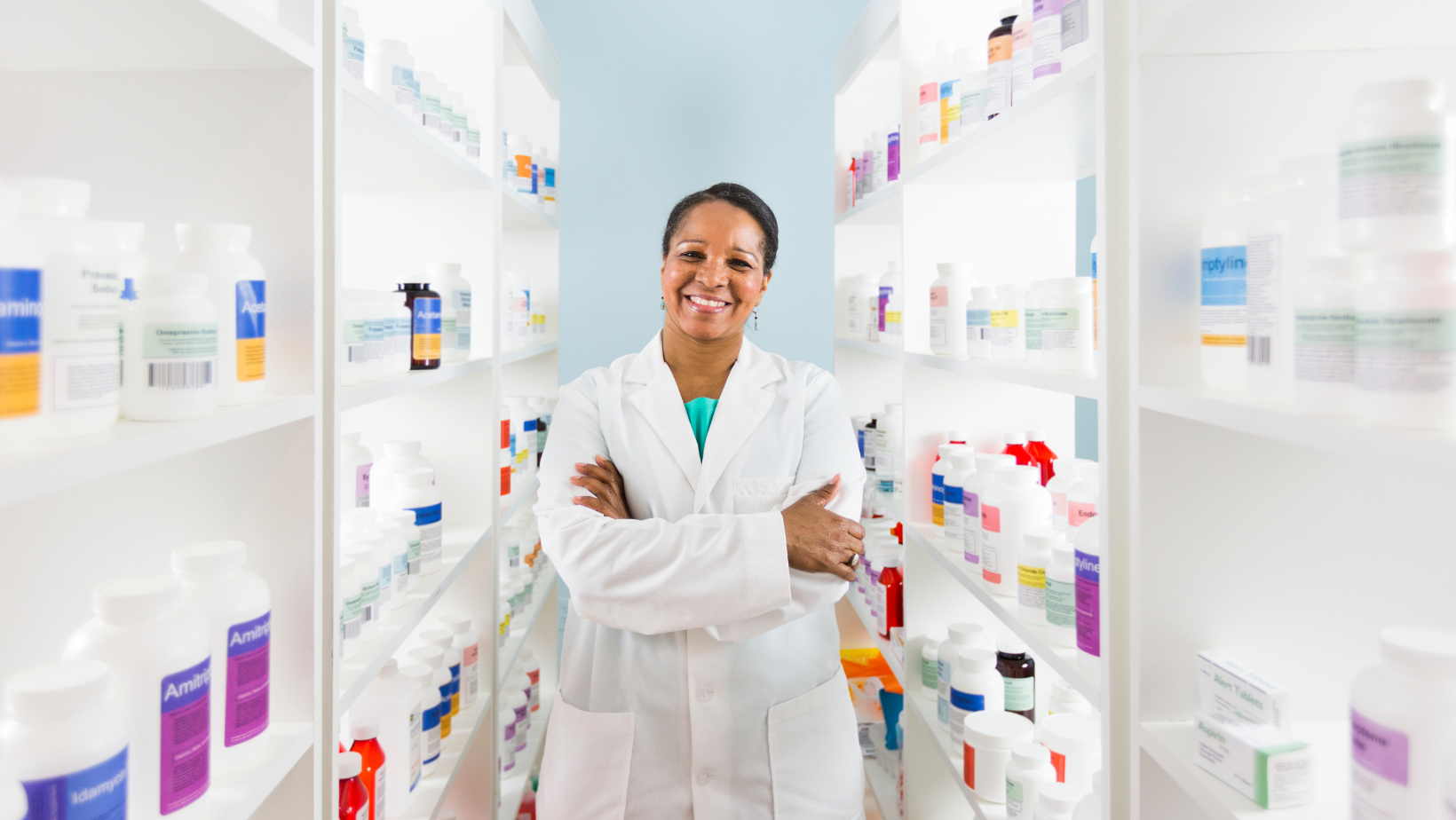 Female Pharmacist standing in the middle of shelves lined with various medications